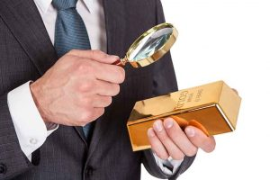 Business professional examining gold with magnifying glass, deciding to buy gold despite market conditions