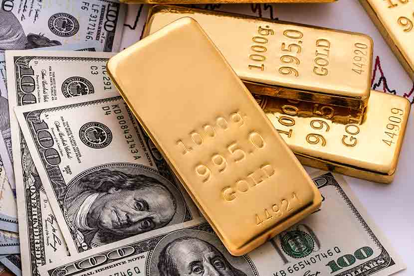 Gold bars stacked on an array of one hundred dollar bills