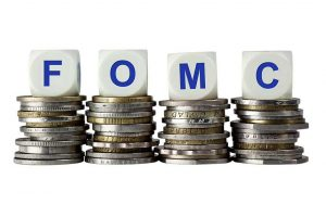 Federal Open Market Committee abbreviation on top of stacks of silver and gold coins