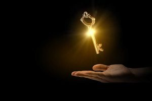 Shining golden key hovering above a hand