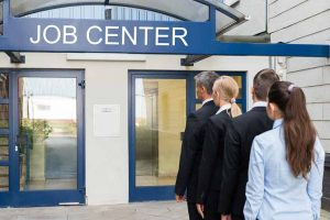 Variety of unemployed professionals lined up outside job center