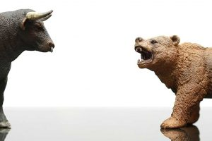 Ferocious bear figurine roaring at a bull figurine