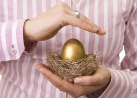 Golden egg in nest protected by hands