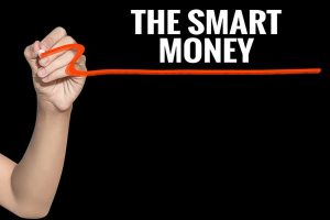 Writing with red pen on board that reads Smart Money