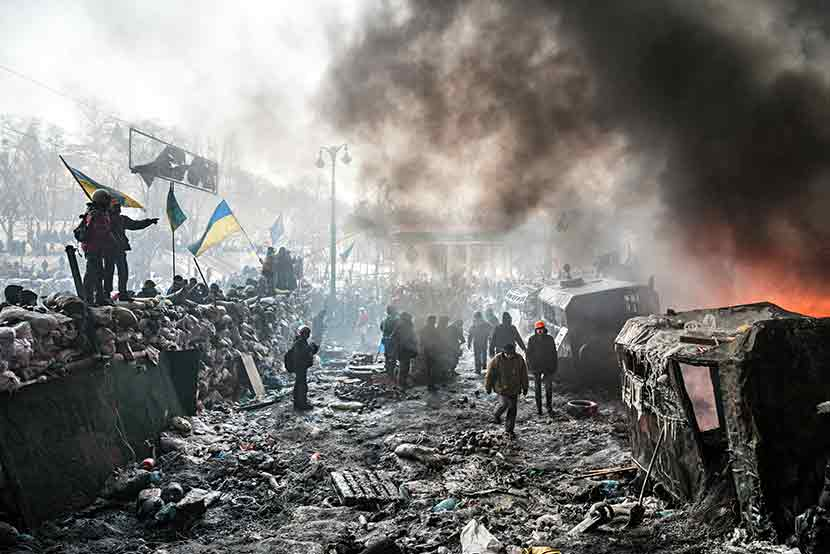 The smoking streets of a war torn Ukraine, citizens and militants walking around in the rubble