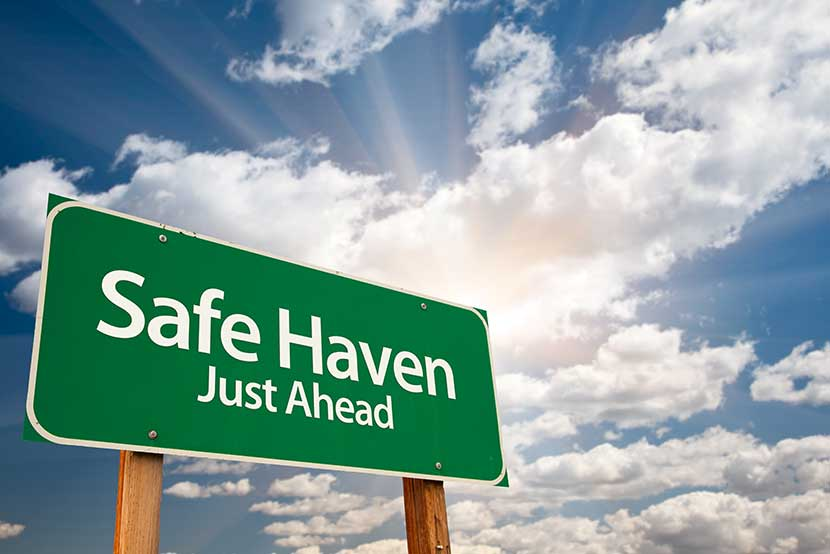 Green safe haven sign with sun breaking through clouds in the background