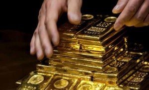 Hands carefully stacking several one kilo gold bars