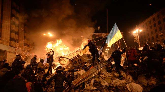 Picture of Ukraine riots in the streets with fire in the background and rioters climbing wreckage with one holding a Ukranian flag