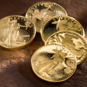 Five Gold American Eagle coins laying down on a table