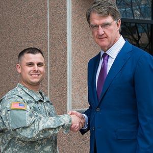 Philip N. Diehl shaking the hand of uniformed U.S. Army soldier Rodriguez