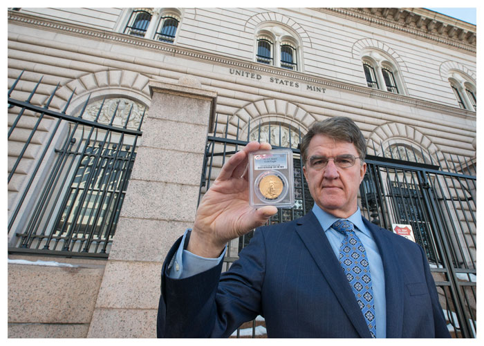 Philip N. Diehl, former U.S. Mint Direct and President of U.S. Money Reserve, standing in front of the U.S. Mint in Denver, CO and holding a gold coin