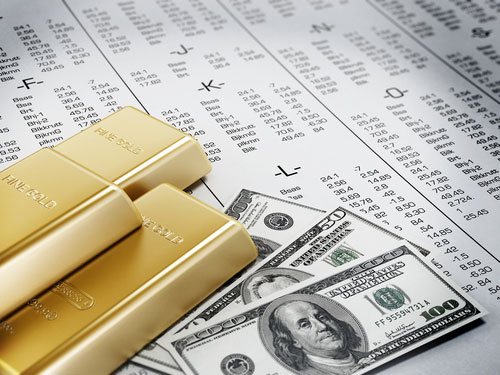 Bars of gold and three stacks of $100 and $50 bills atop an alphabetized list of stocks