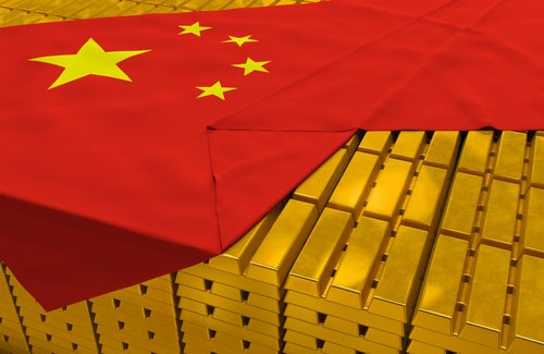 Massive expansive of stacked gold bars peeking out from under Chinese flag, draped over them