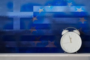 Greek flag juxtaposed over European Union flag with white retro clock sitting in front, moments away from unrest