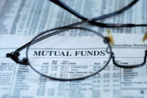 Mutual funds section of newspaper with pair of eyeglasses magnifying the newspaper heading