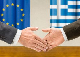 Greece and European Union strike a deal after marathon talks, as illustrated by two hands extending for a handshake