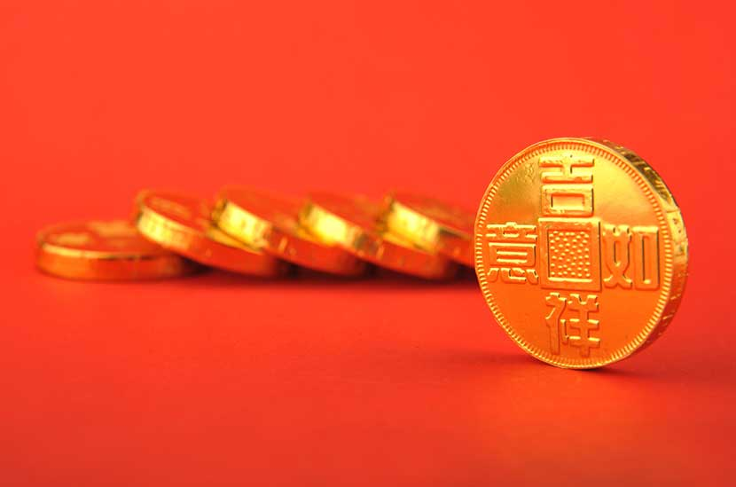 Fallen stack of Chinese gold coins against bright red backdrop