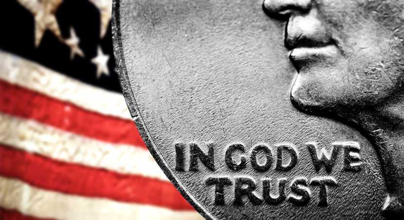 Magnified words on U.S. quarter, In God We Trust, against backdrop of American flag
