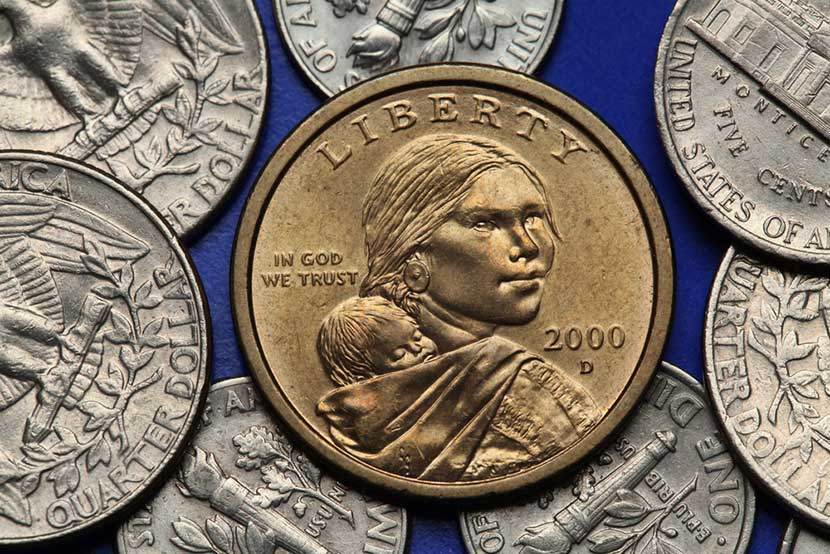 Pile of dimes, quarters, and nickels with Sacajawea one dollar coin in front