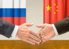 Two hands extending towards one another, representing China and Russia shaking hands
