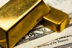 One large gold bar and one small gold bar atop crisp United States dollar bills