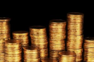 Various stacks of gold coins at different heights against pitch black background