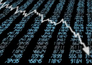 Jagged, falling arrow against backdrop of electronic stock prices