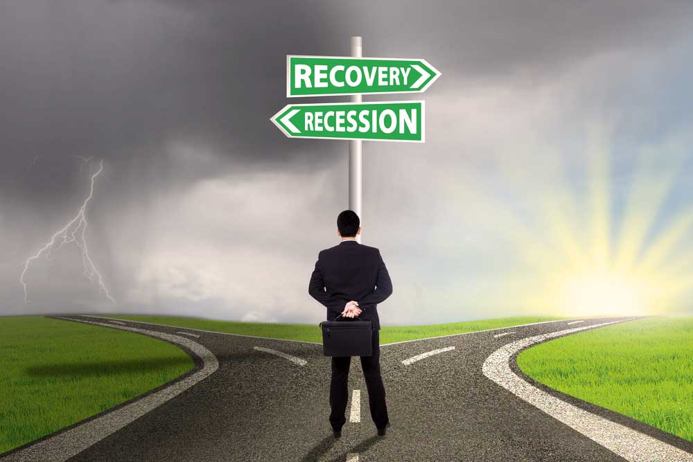 Businessman standing at crossroads of recovery and recession. Recovery points to a cheerful sunrise, while recession points to a dark thunderstorm.