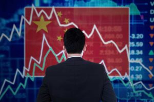 Chinese businessman staring at stock market screen as China stock trading halts after steep drop