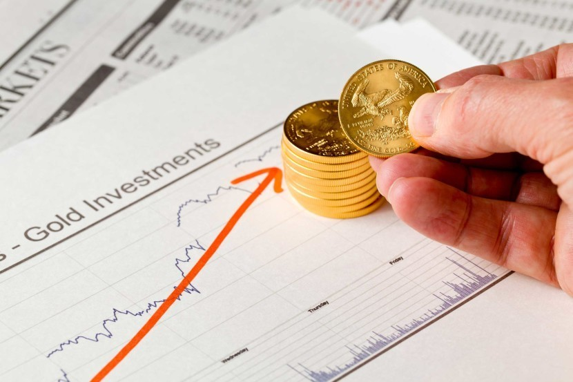 Man holding gold coins and looking at gold investments report with red arrow indicating gold gaining as stocks rout