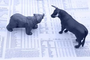 Bear and bull figurines standing off atop newspaper of stock market news