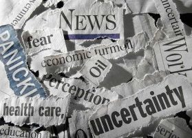 Torn pieces of newspaper with words like uncertainty, health care, oil, economic turmoil, and panic