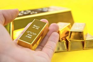 Hand holding 200 gram fine gold bar with stacks of larger gold bars in yellow background