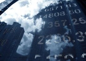 The reflection of clouds and city buildings on digitally displayed stock market prices