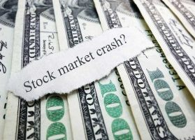 "One hundred dollar bills neatly lined up with a torn piece of paper reading ""stock market crash?"""