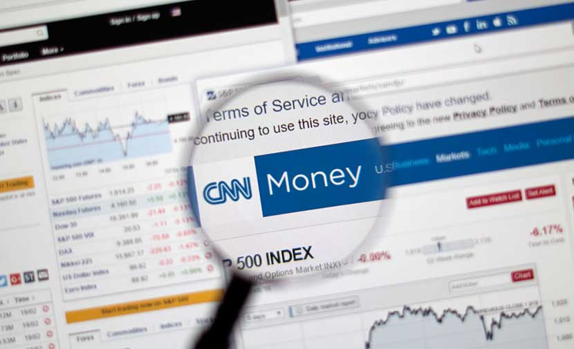 Magnifying glass hovering over CNN Money website