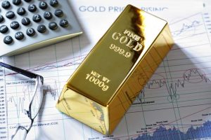 Fine gold bar sitting on stock market reports with calculator