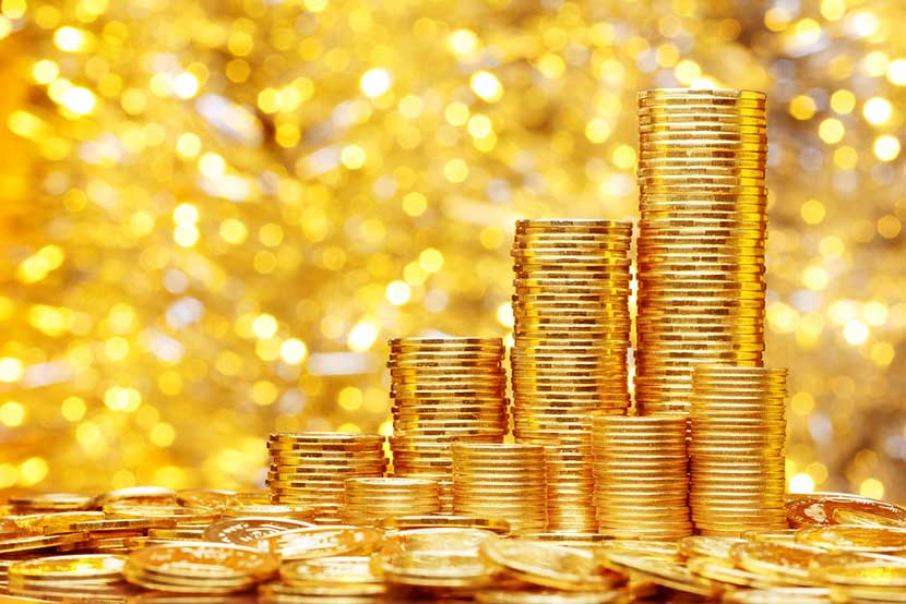 Gold coins stacked against a glittering gold backdrop