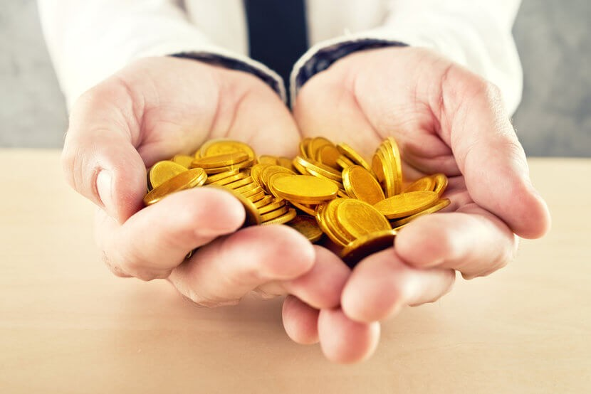 Man dressed in business attire holding gold coins, wondering whether to buy gold locally or buy gold online