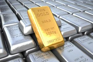 Fine gold bar leaning on rows of silver bars