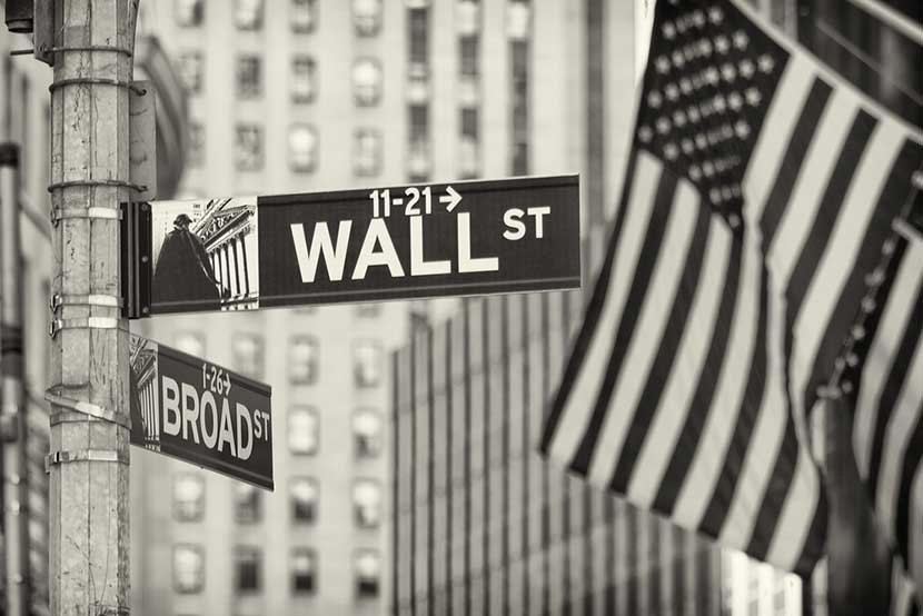 Black and white street sign showing corner of Wall Street and Broad Street, lined with U.S. flags