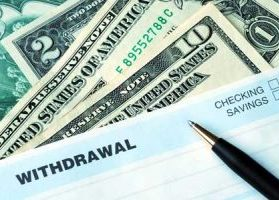 Withdrawal slip and various denominations of cash, as customer withdraws cash from bank