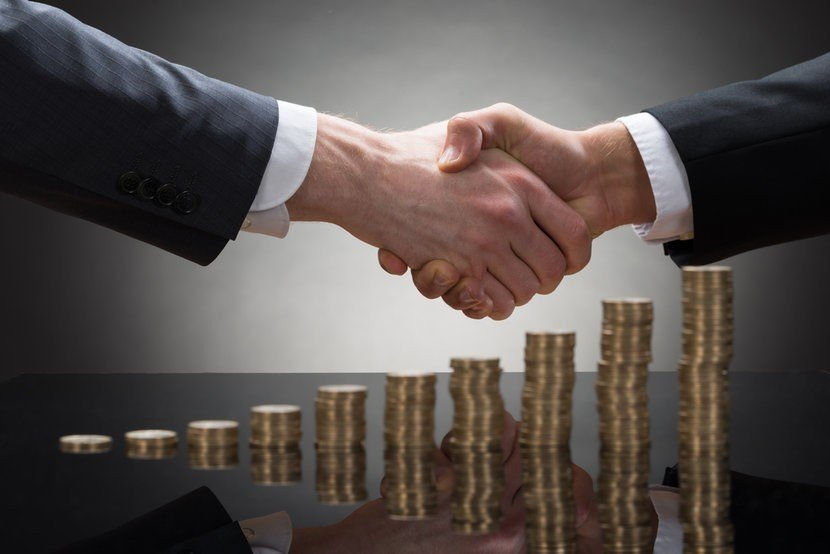 Two business men shaking hands over stacks of gold coins