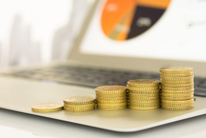 Ascending stacks of gold coins sitting atop a laptop, with financial portfolio on computer screen in background