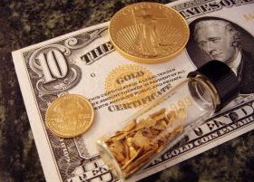 Gold coins, gold flakes in capsule, sitting on top of ten dollar bill