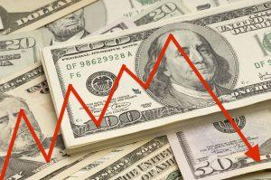 Various denominations of U.S. bills, with red arrow overlay indicating weak economy