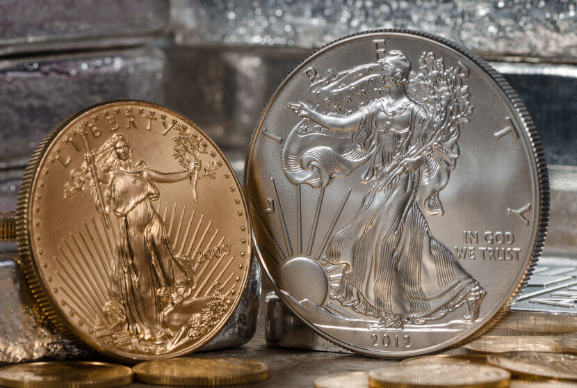 American Gold Eagle Coin next to Silver Eagle Coin, against a backdrop of silver bars
