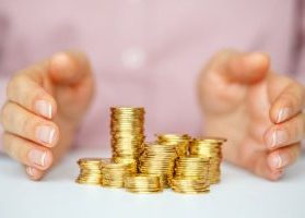 Woman in pink shirt with hands protecting pile of gold coins