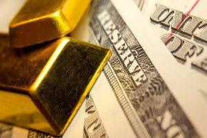 """Two gold bars overlaid on top of U.S. currency, close up view of """"Reserve"""""""