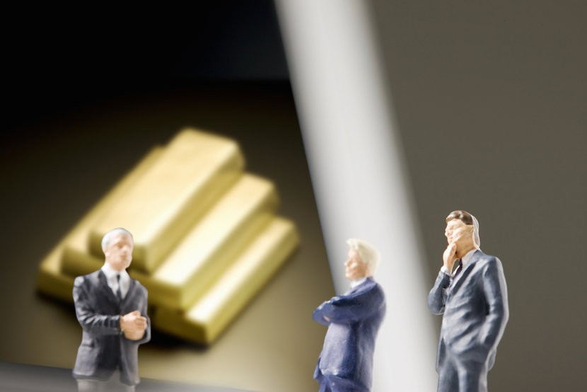 Politician figurines in front of gold bars, discussing future of gold